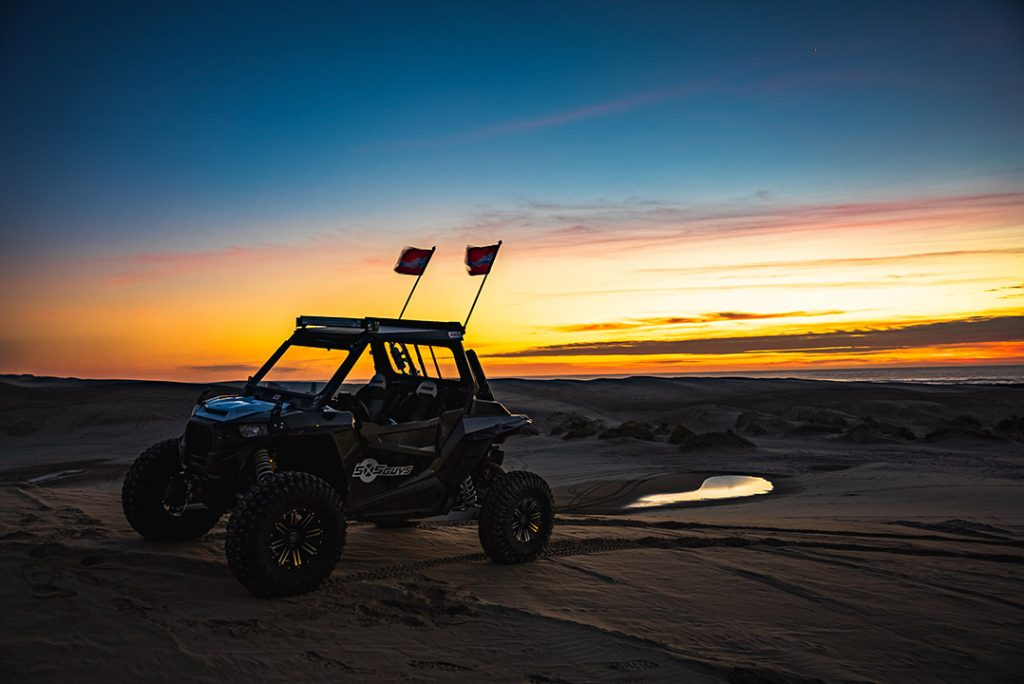 A UTV perched upon a small dune as the sunset hides behind clouds.