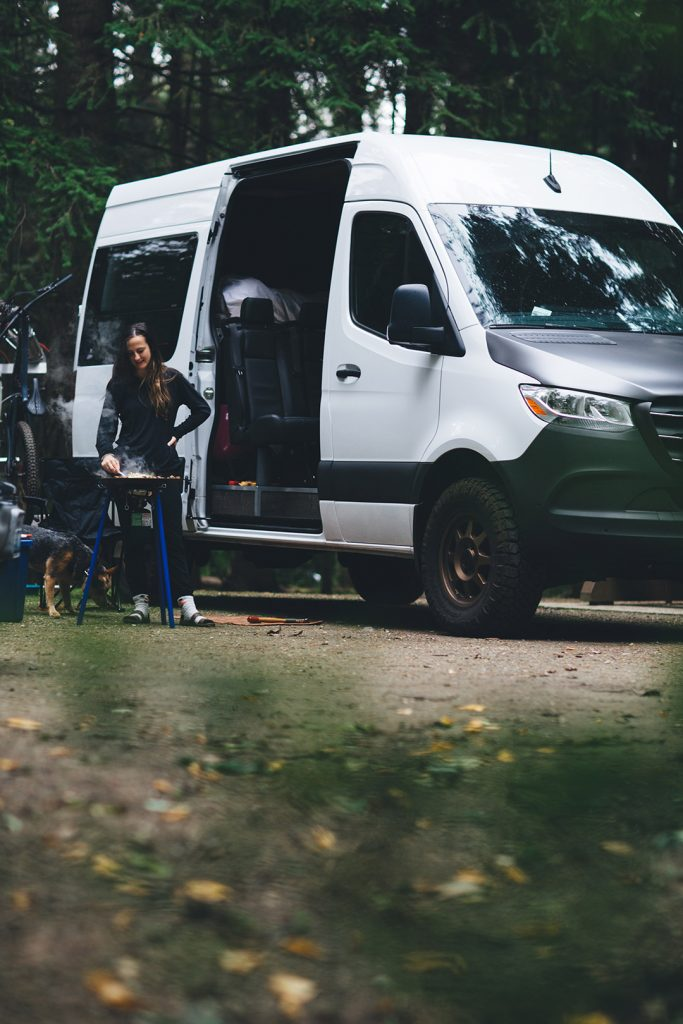 Cameron's companions camping in his van and preparing a meal in the woods.