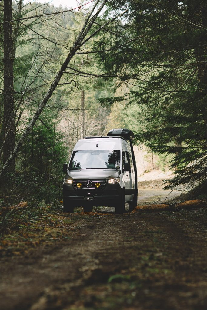 Cameron's van parked on a dirt road in the woods.