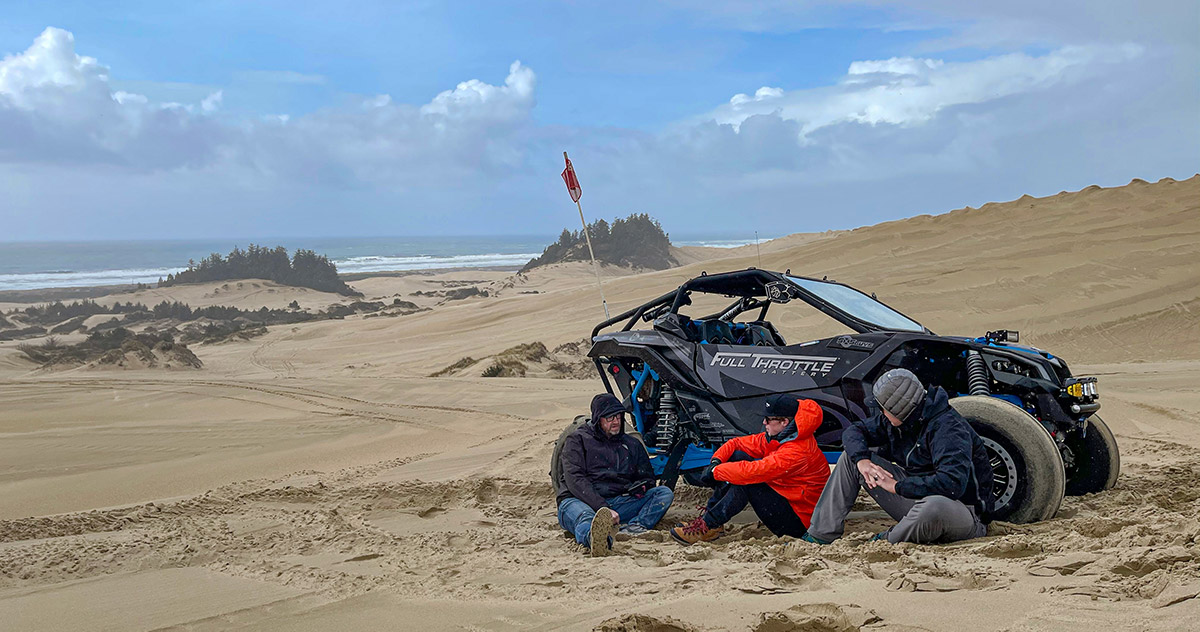 A group of guys enjoying the beach while taking refuge from the wind in Winchester, Oregon.