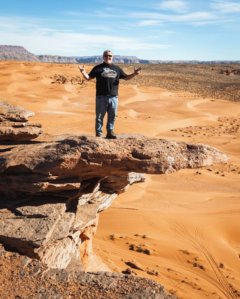 David Schumacher stands on a cliff overlooking a picturesque landscape in Sand Hollow State Park (Hurricane, Utah).