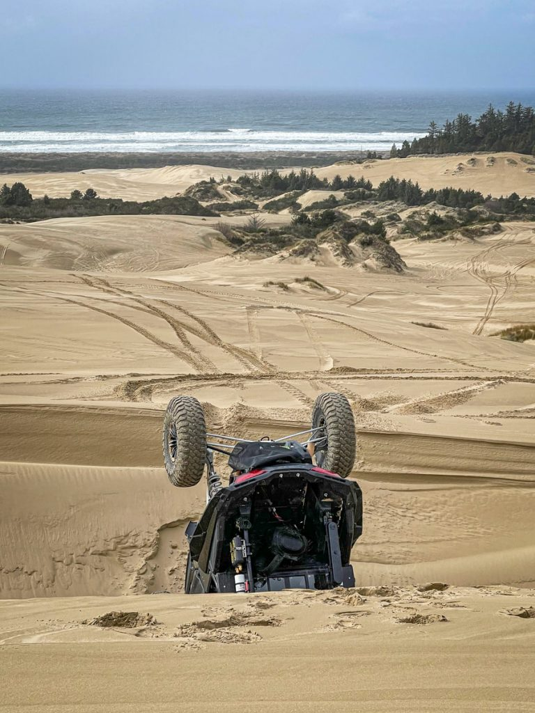 The SxS Guys UTV flipped upside down with the beach in the background.