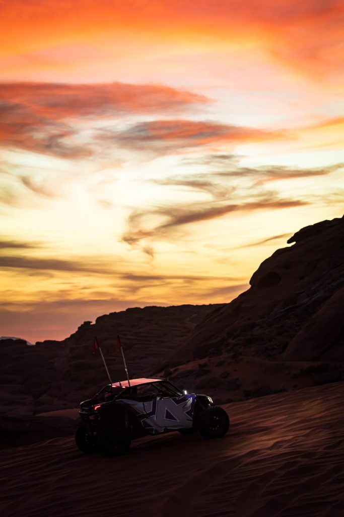 The Amped UTV on a sand dune during sunset.
