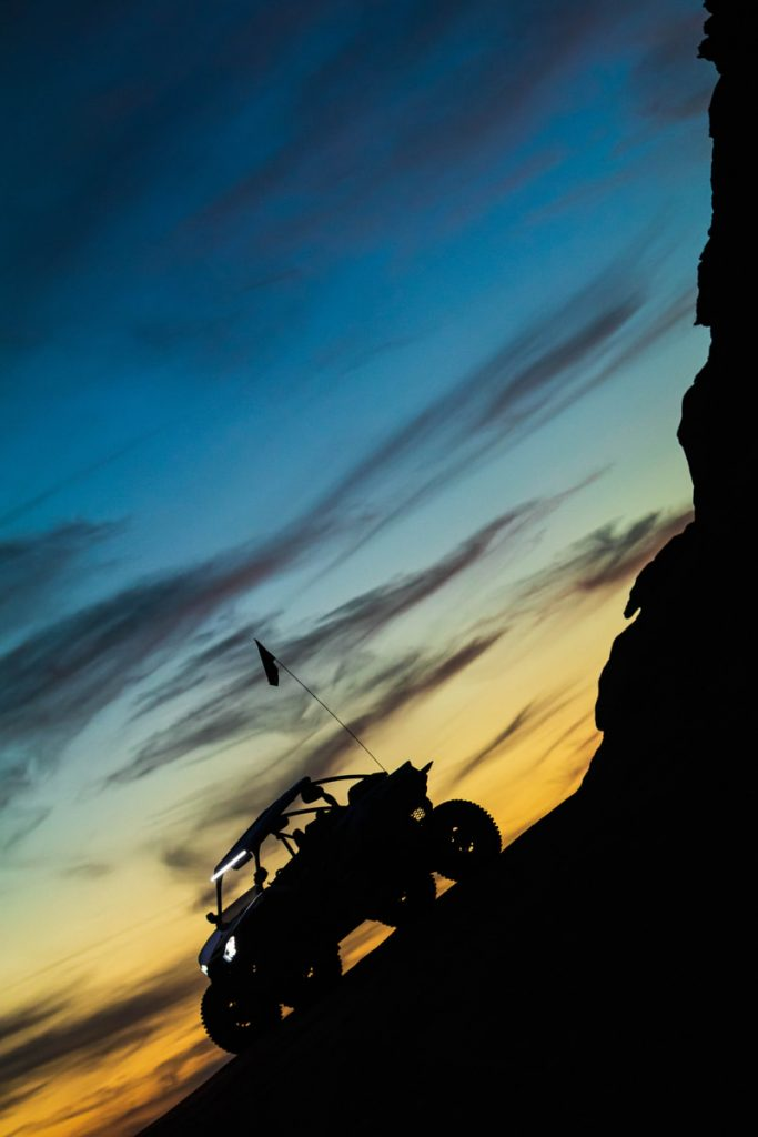 A silhouette of a UTV during blue hour near a cliff face.