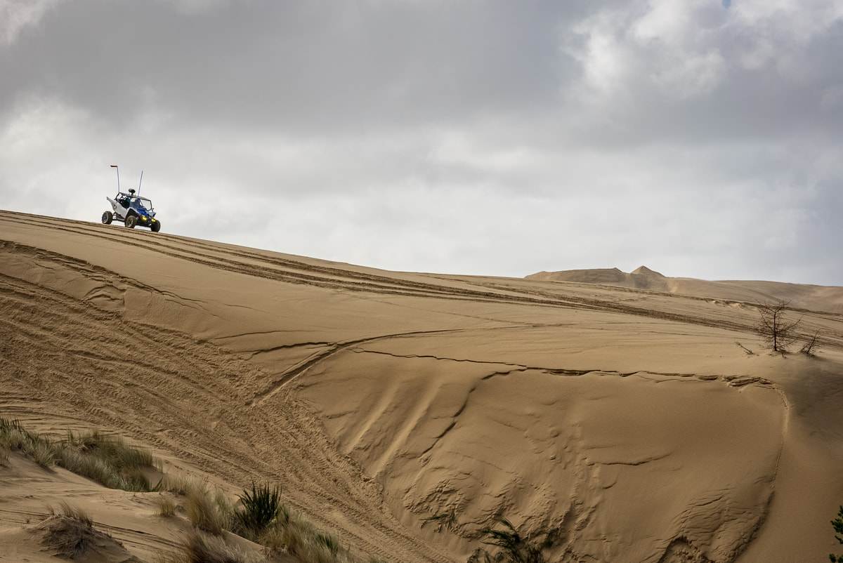 A UTV sits on top of a large sane dune during an overcast day.