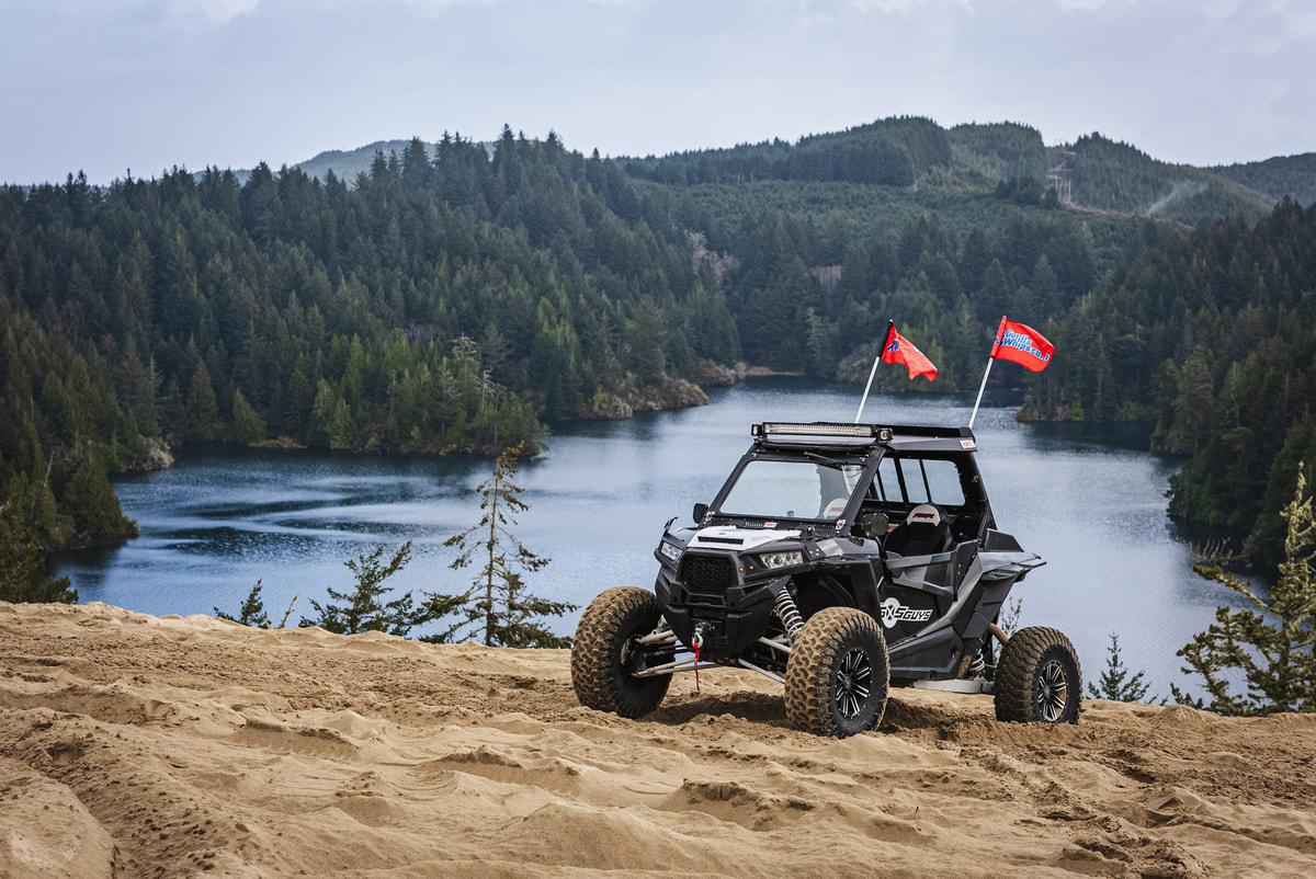 The SxS Guys UTV sits in front of the beautiful lake surrounded by a forest.