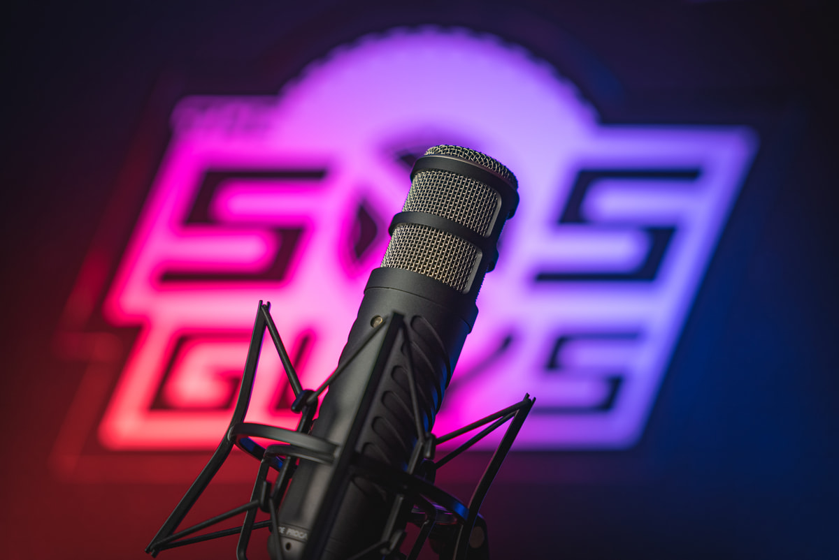 Microphone in front of the SxS Guys logo.